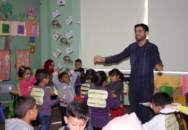 Core Early Childhood teacher Mahmoud leads his class as the students as they wear bee wings and pretend to fly around the classroom.