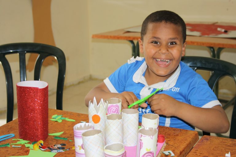 Core student Mohammad smiles as he works on a project during art class.