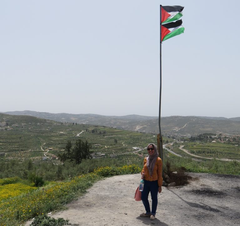 Haya poses with the Palestinian flag on a sunny day in Sebastia, a village on the outskirts of Nablus.