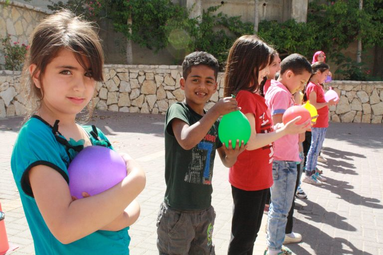 Core students Minna and Yoseph hold their water balloons as they prepare for a balloon toss.