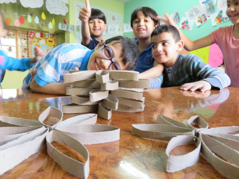 Children make flowers out of recycled paper towel rolls during their Core class.