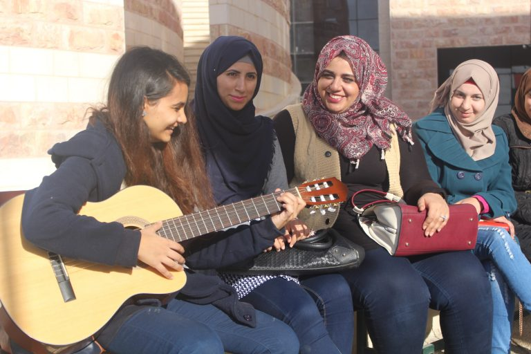 Students Nihaya, Rawia, Dania, and Ala'a of the STEP! II EFL program take a break to enjoy some music and sunshine with their classmates.