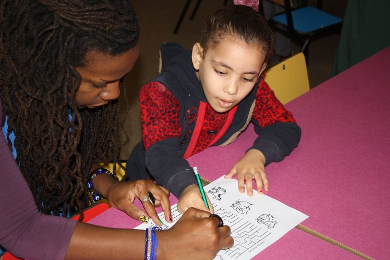 Learning together can be fun! A Core AM student learns about animals while EFL Fellow Mecca assists with a maze.