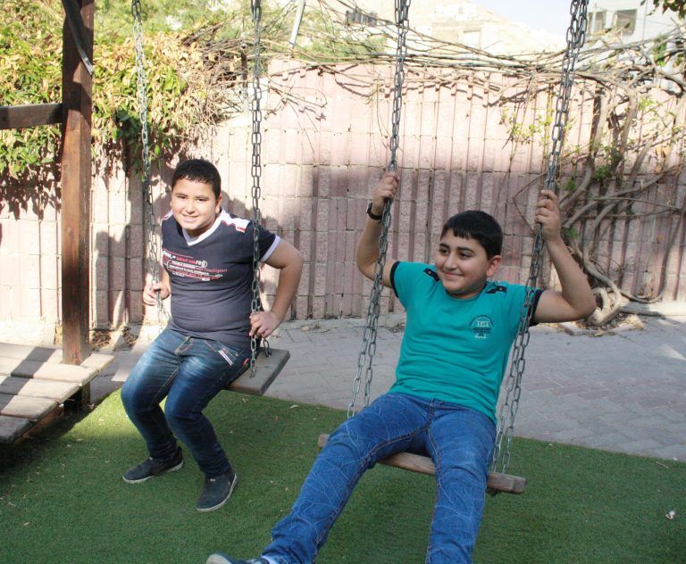 Ahmed and Amir, two students in the academic support program, have some fun between classes.