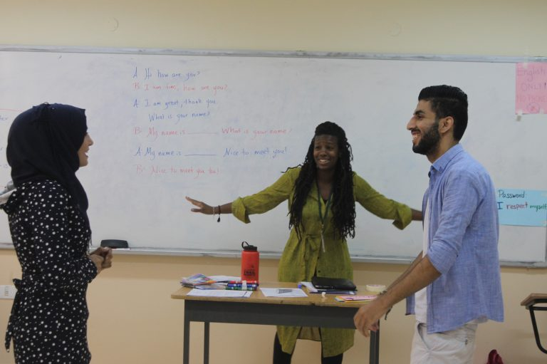 Everyone smiles as they participate in an English learning activity.