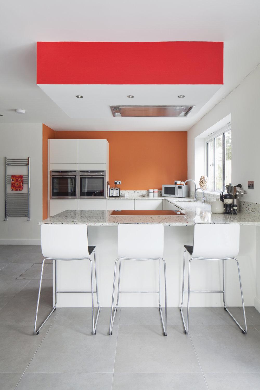 modern white kitchen with pops of orange