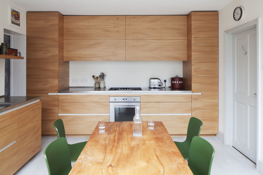hand made natural timber kitchen with green chairs