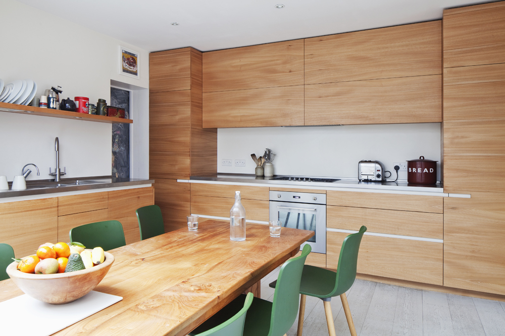 contemporary natural timber kitchen and green chairs