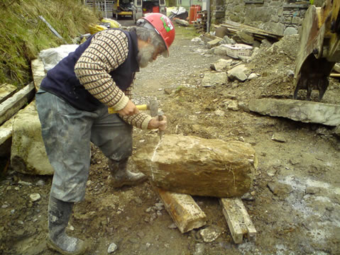 man chiseling stone for barn conversion
