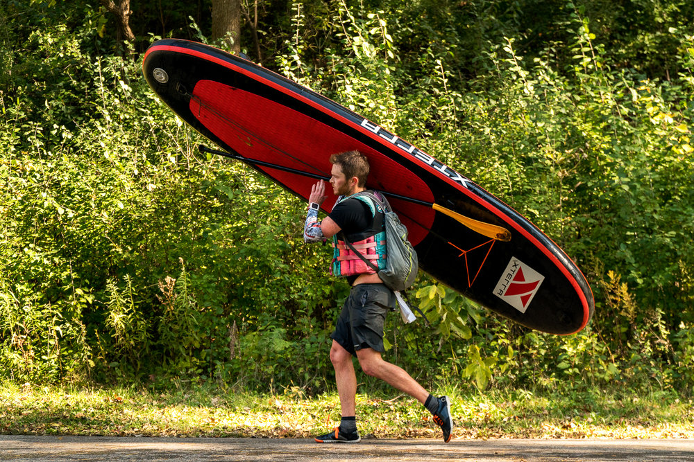 A stand up paddleboarder portages from Bassett Creek en route to Wirth Lake.
