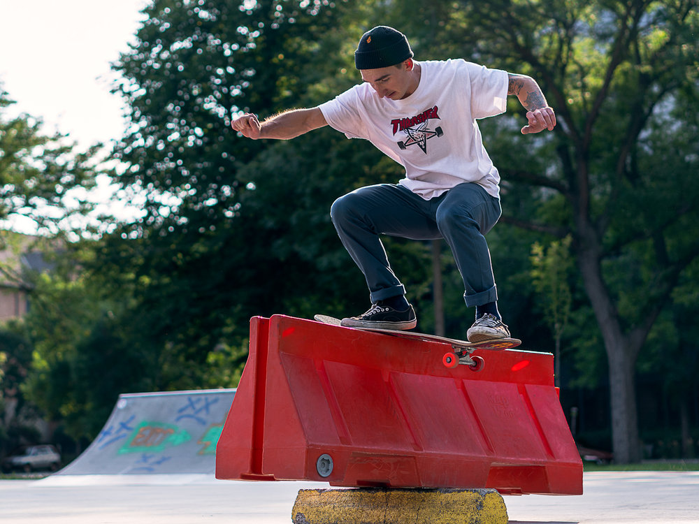 Andrew Helminiak backside boardslides up one side of a teeter-tottering barricade and back down the other at Elliot Park in Minneapolis, Minnesota.