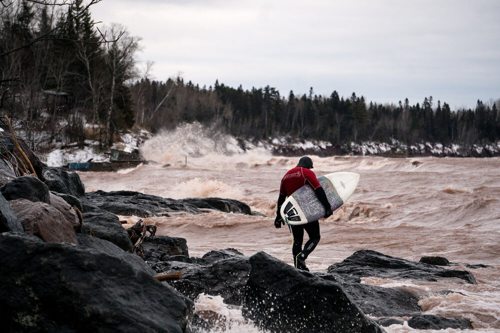 Ryan Patin paddles out into the icy waters of Lake Superior wearing a Mexico surf jersey.