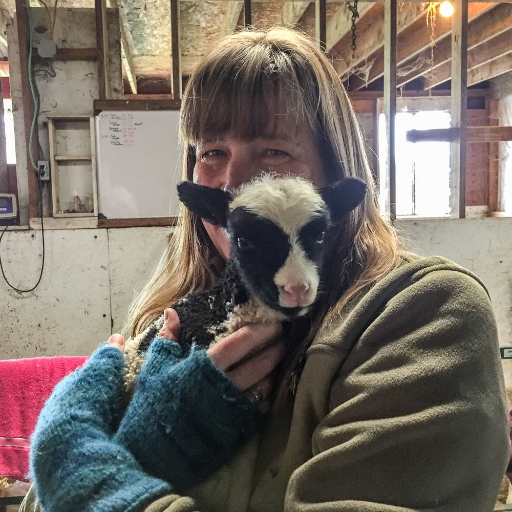 Lisa holding a lamb.