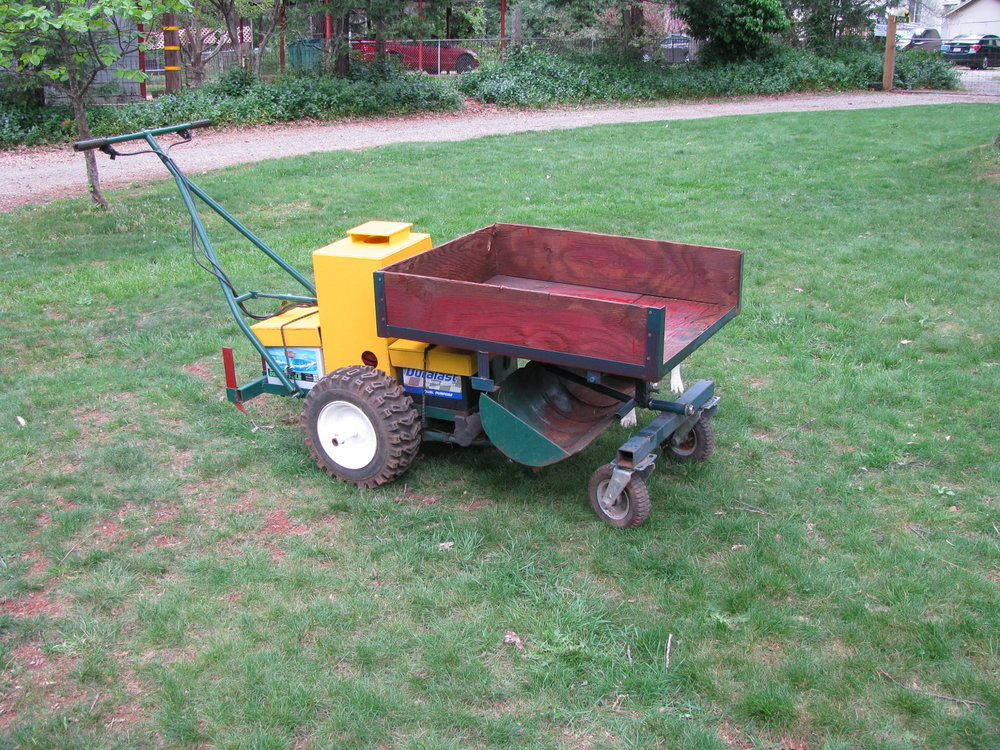 The Electric Walk Behind Tractor (EWT) with dump bed, bucket and rippers on. All wrapped in one tidy package.