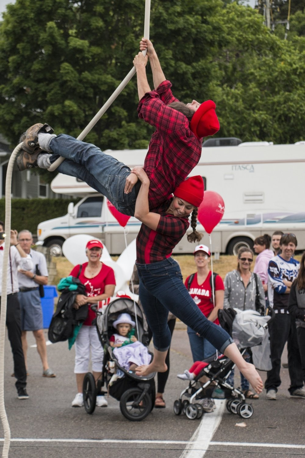 Female lumberjack hanging off male lumberjack holding onto aerial rope