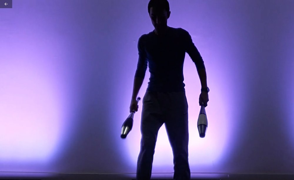 Juggler with clubs in front of blue light