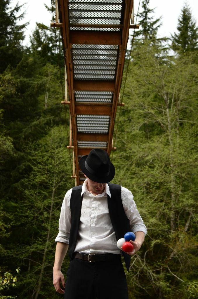 Juggler in black fedora under suspension bridge with multicoloured balls