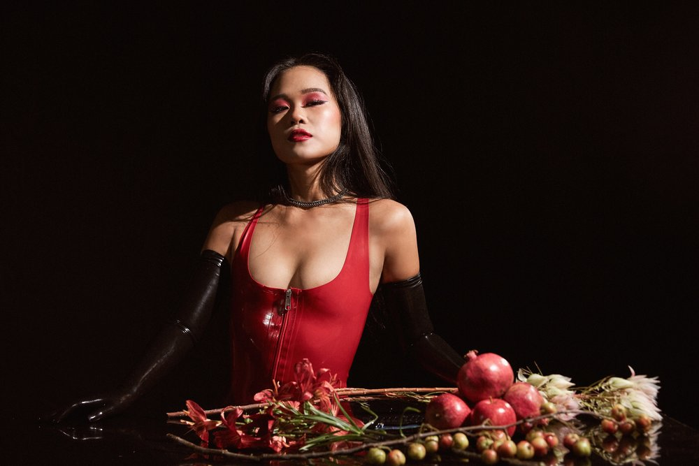 Asian female dominatrix Empress Wu in a red latex dress and black latex opera gloves surrounding by the spoils of luxury