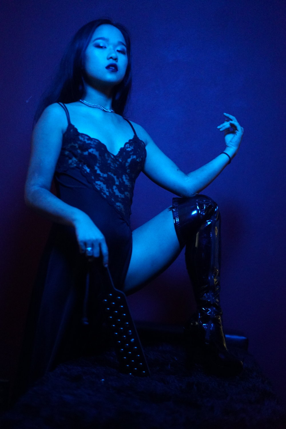 Asian New York professional dominatrix Empress Wu holding the impact tool she most prefers for doling out torture