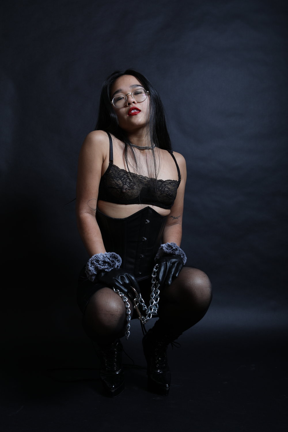 Empress Wu, NYC prodomme and BDSM professional, in a leather corset holding the chains with which she wants to put you in bondage
