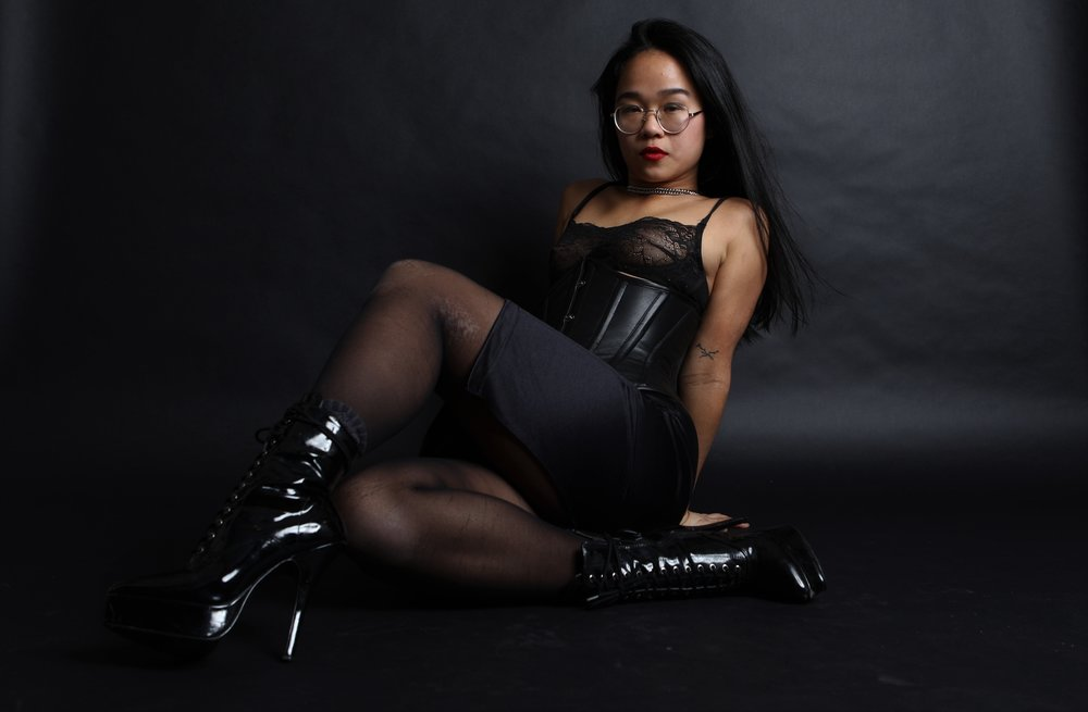 BDSM professional and NYC femdom Empress Wu looks at you over her black vinyl boots. She is wearing a black leather corset, lace lingerie, and sheer black nylon stockings.