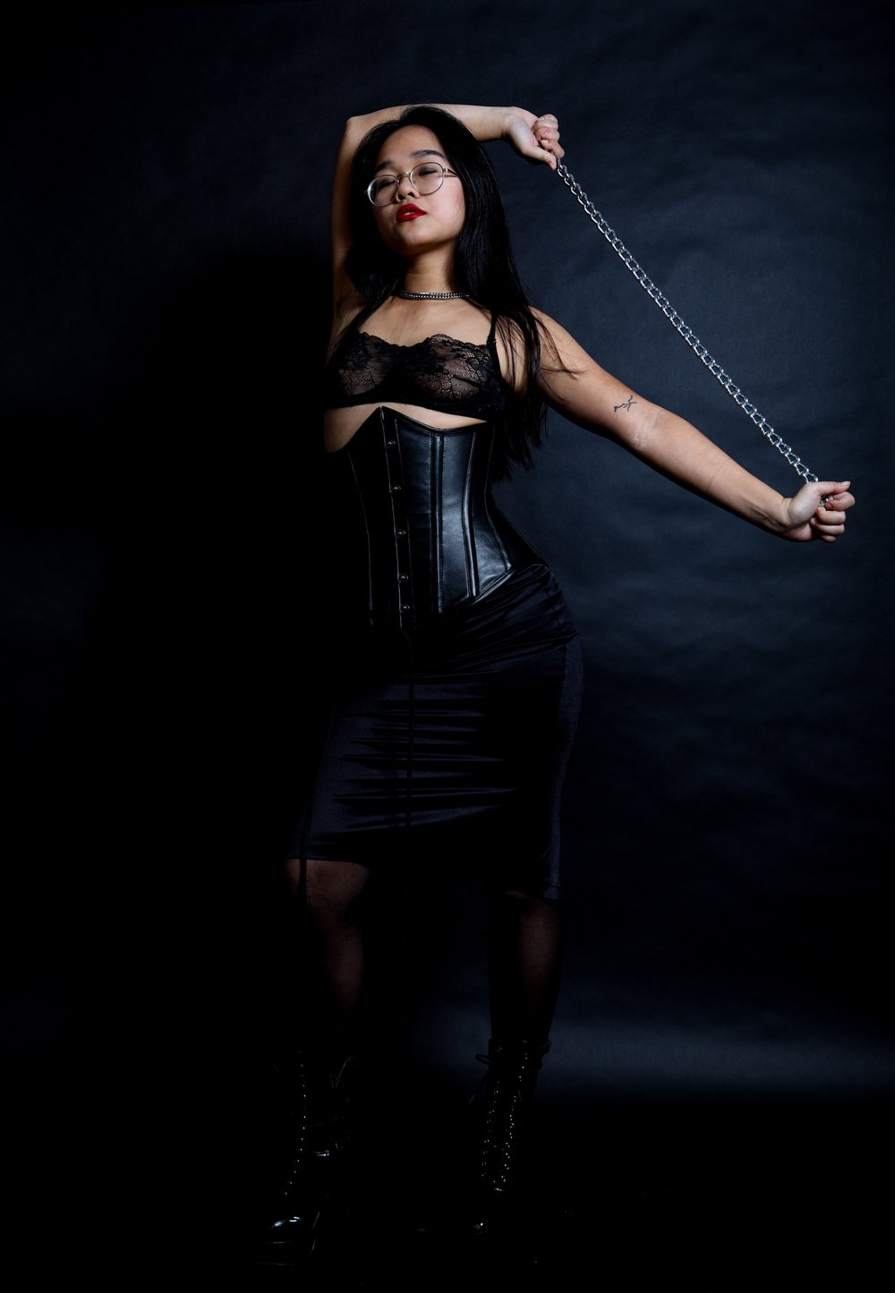 Chinese Dominatrix Empress Wu In an all black outfit: lingerie, leather corset, nylons, and vinyl boots, New York Prodomme is ready to take all of your fetishes