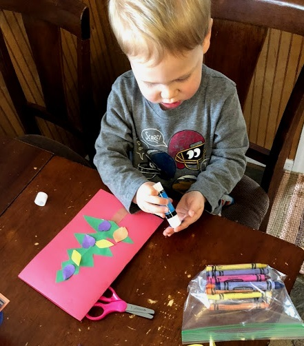 Emerson (2) glues the ornaments on trees for holiday cards to send his friends.