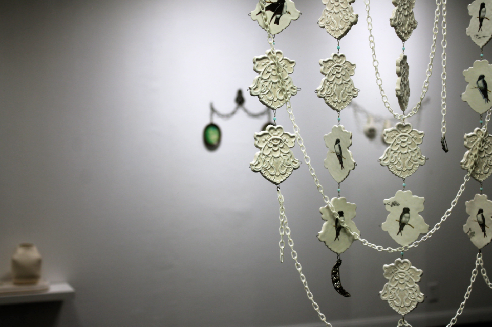 Swallows (foreground),  porcelain, decals, nylon chain and opals, 2018, detail view.