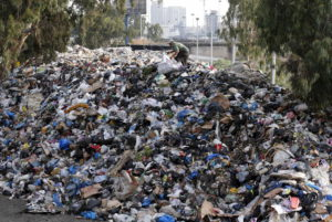 A scavenger sifts through garbage piled on the bank of Beirut river, Lebanon. Source: Wikicommons