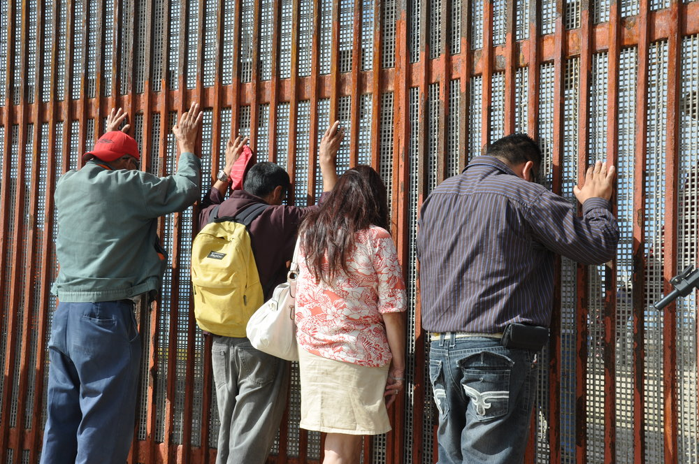 Mexican deportees standing at the U.S.-Mexico border