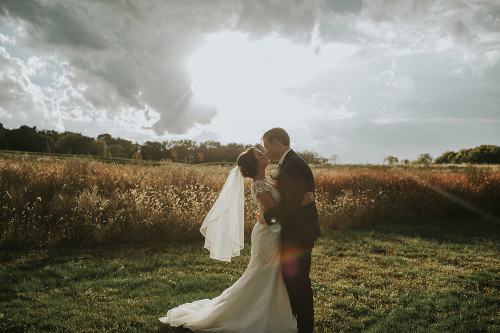 Amanda & Brian embrace on their wedding day in a field at sunset.