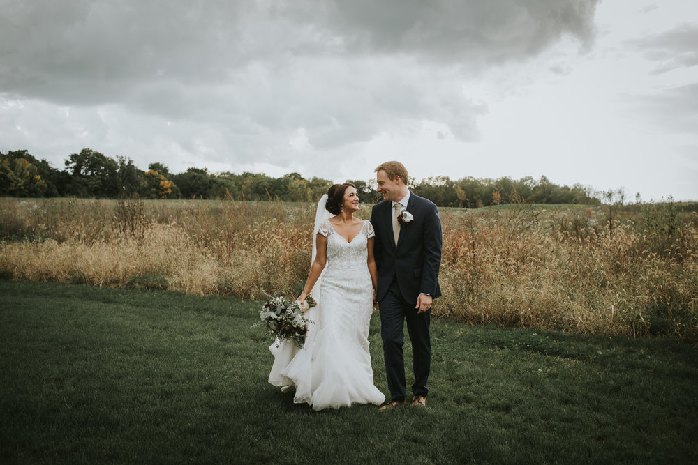 Bride & Groom smile at each other in field