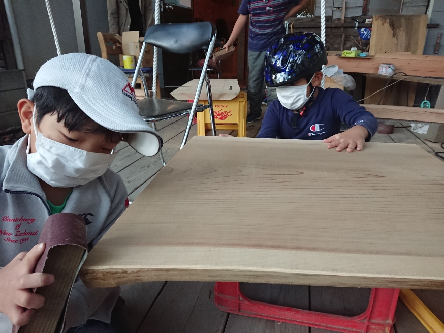 The boys are  sanding  the table.