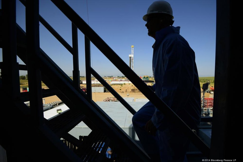 James Schwaberow | Bloomberg | The silhouette of a contractor is seen walking up stairs at an Anadarko Petroleum Corp. oil rig site in Fort Lupton.