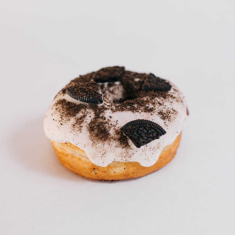 The Dirty - Yeast risen and deep fried doughnut dipped in vanilla glaze topped with cookie crumbles and Oreo pieces.
