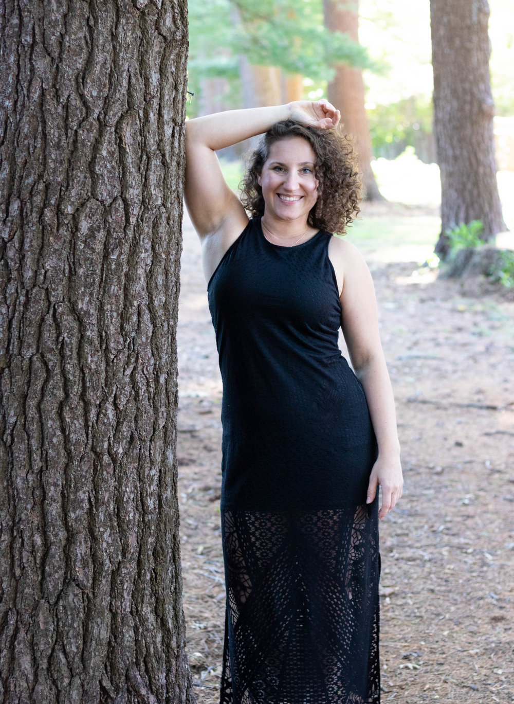 Lifestyle portrait of a woman wearing a black dress leaning on a tree in a park in Newburyport, MA by Vision Balm in Charleston, SC.