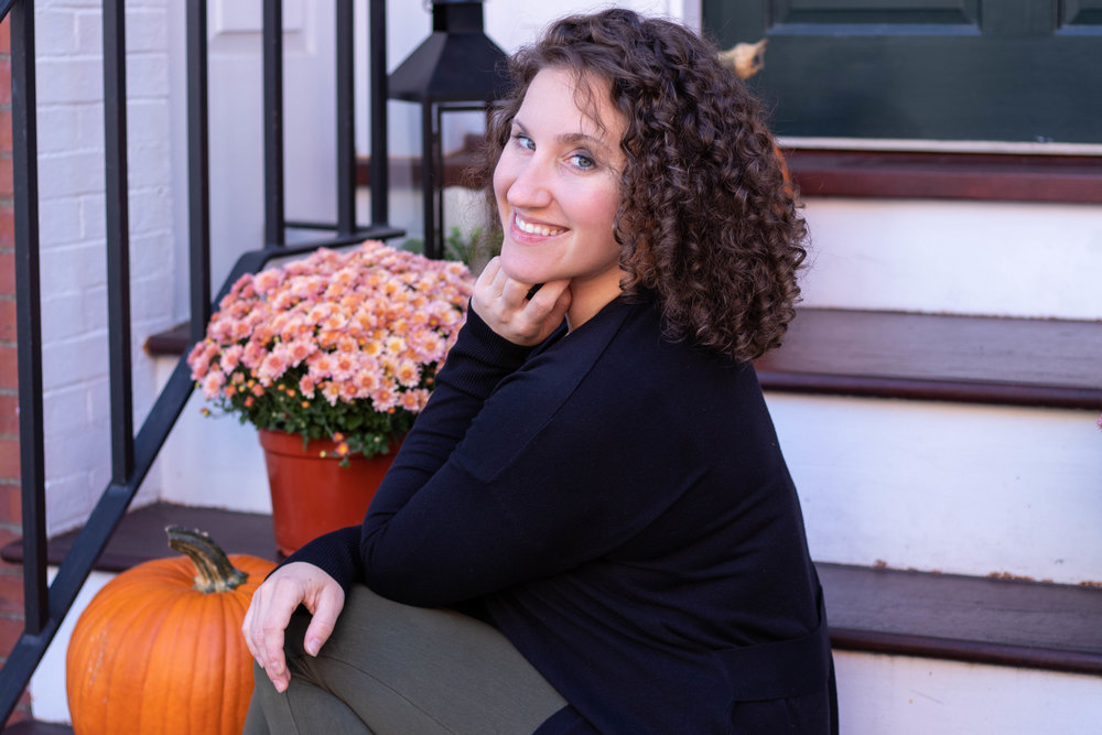 Professional portrait of a woman with curly hair wearing black sitting on stairs in Newburyport, MA by Vision Balm in Charleston, SC.