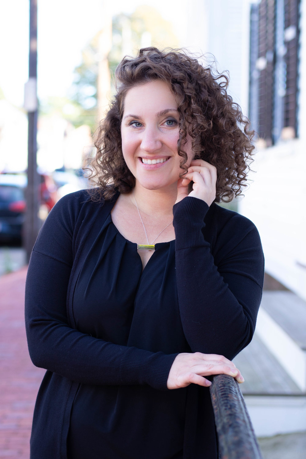 Professional portrait of a woman with curly hair wearing black in Newburyport, MA by Vision Balm in Charleston, SC.