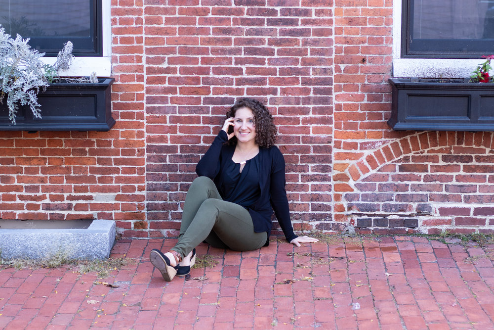 Lifestyle portrait of a woman leaning against a brick wall in Newburyport, MA by Vision Balm in Charleston, SC.