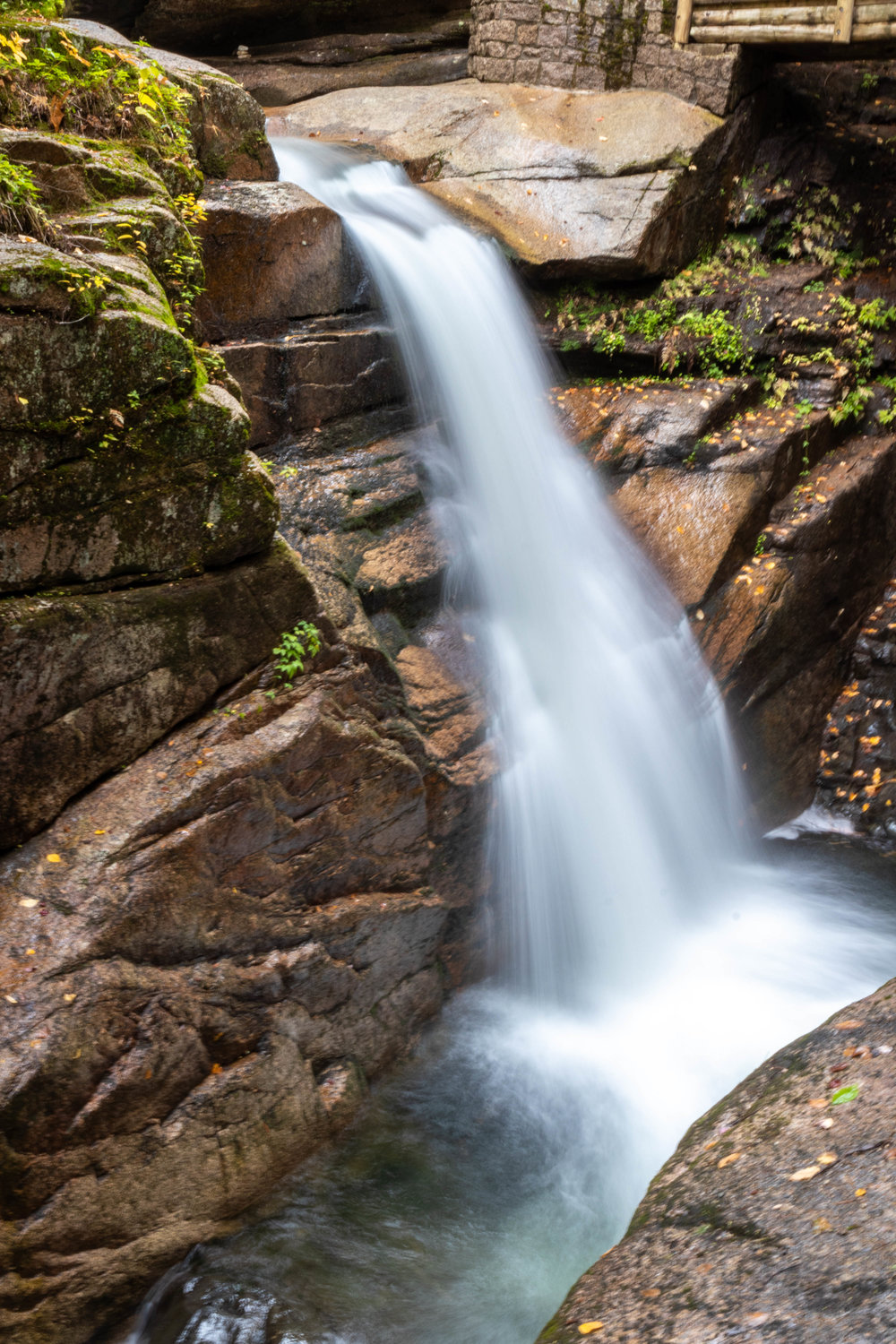 Landscape photo of a waterfall along the Kancamagus Highway in North Conway, New Hampshire by Vision Balm in Charleston, SC.