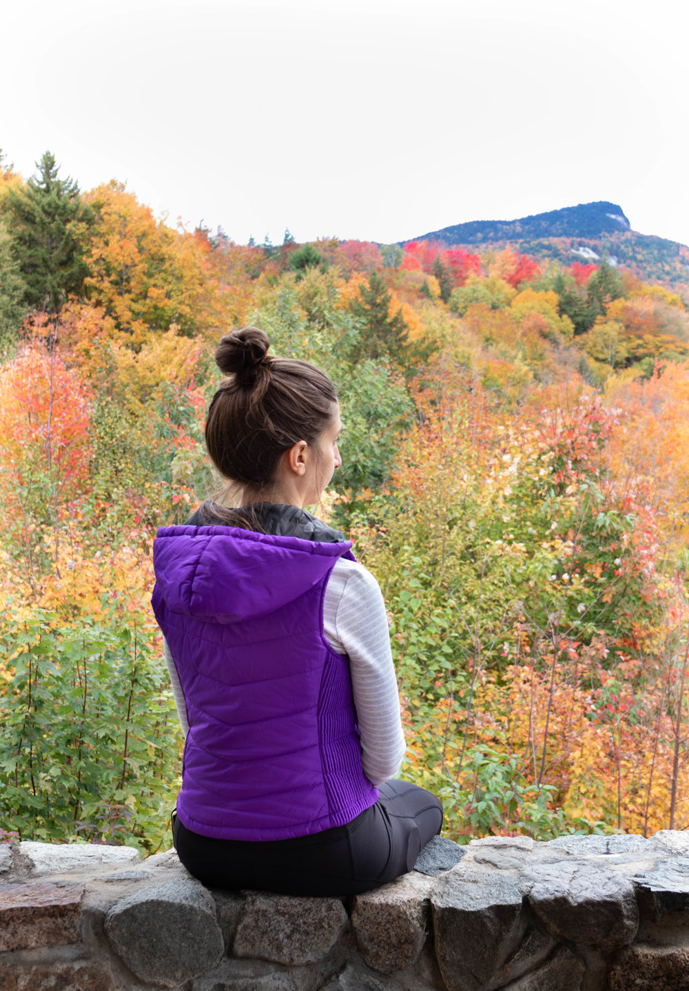 Lifestyle portrait of a woman wearing a purple vest overlooking into the fall foliage along the Kancamagus Highway in North Conway, New Hampshire by Vision Balm in Charleston, SC.