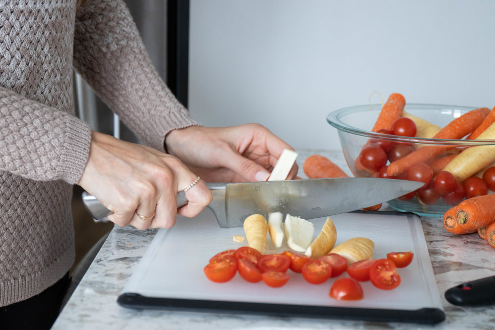 Lifestyle photo of Erin Kenney, registered dietitian of Nutrition Rewired, cutting vegetable in her kitchen in Boston, MA by Vision Balm in Charleston, SC.