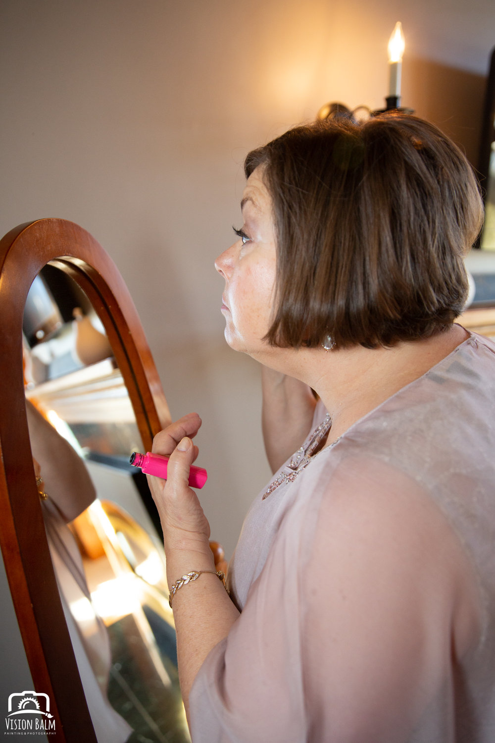 Lifestyle portrait of bride's mother putting makeup on for the wedding in Zuka's Hilltop Barn by Vision Balm in Charleston, SC.
