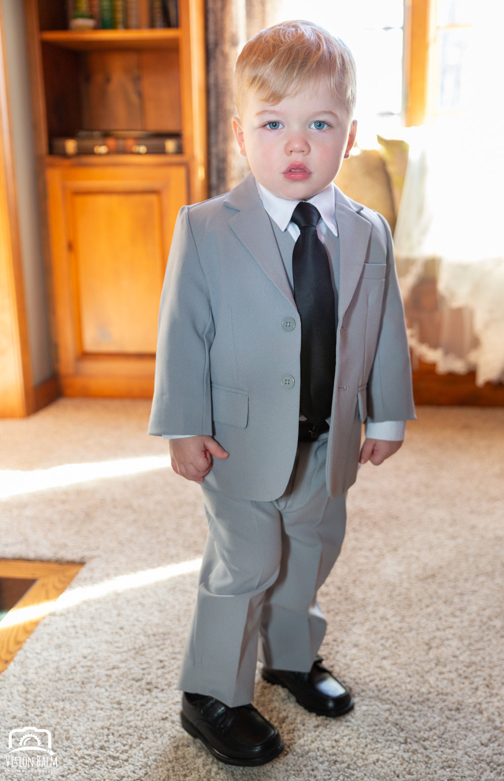 Portrait of young boy dressed in a gray suit for his mother's wedding in Zuka's Hilltop Barn by Vision Balm in Charleston, SC.