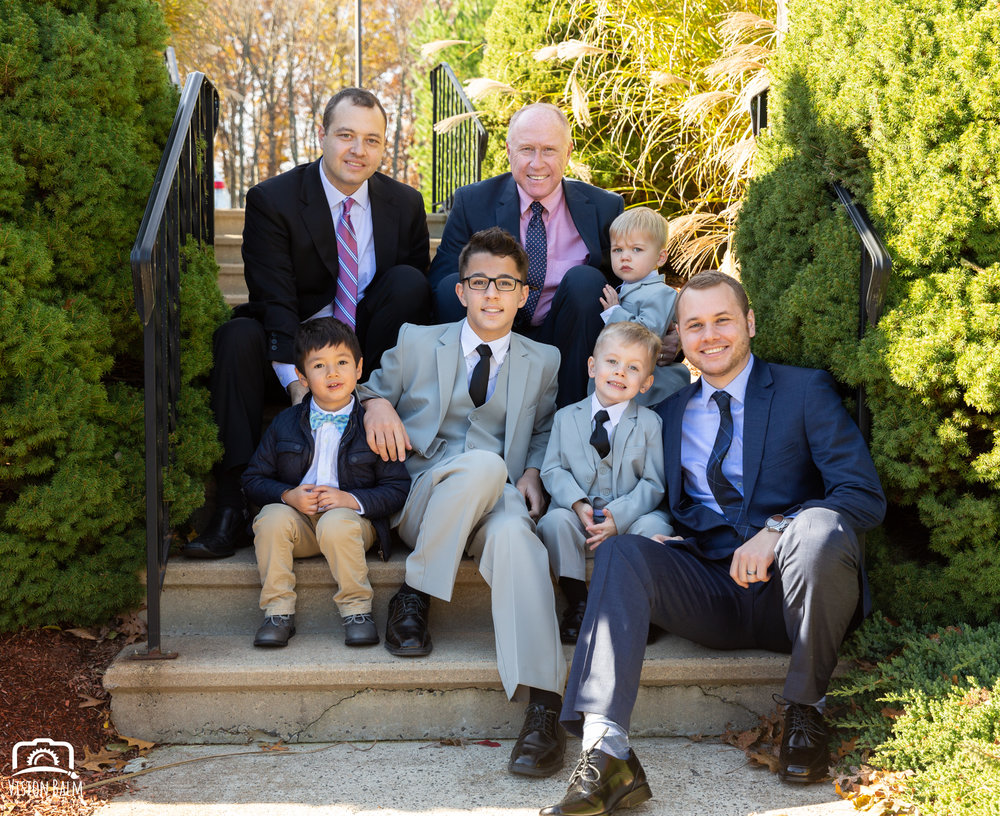 Lifestyle family photo of men in suits sitting on the stairs before wedding in Zuka's Hilltop Barn by Vision Balm in Charleston, SC.