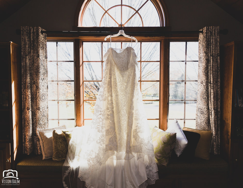 Wedding details photo of bridal gown / dress hanging in the bridal suite in Zuka's Hilltop Barn by Vision Balm in Charleston, SC.