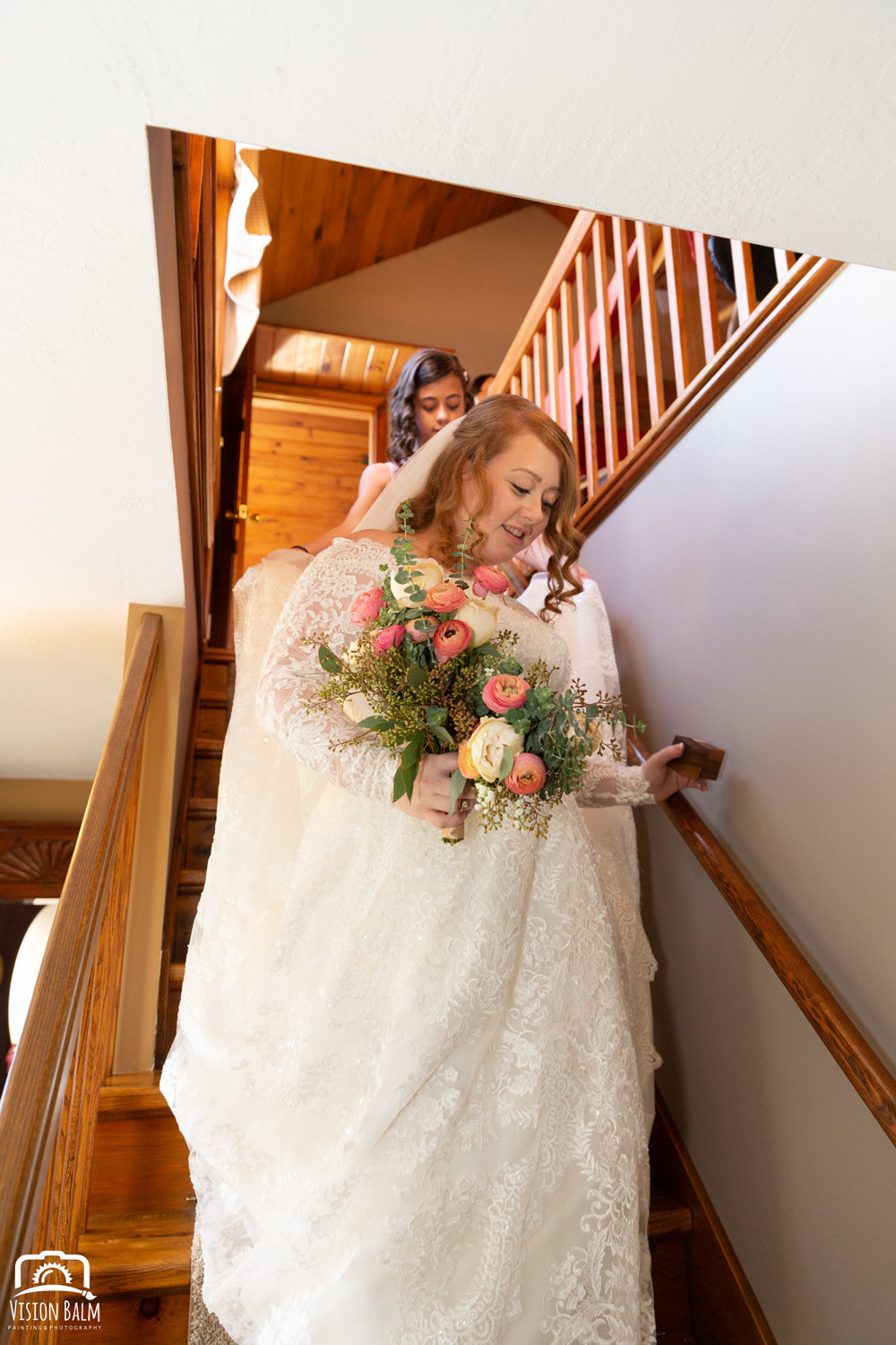 Lifestyle wedding photo of bride walking down the stairs in Zuka's Hilltop Barn by Vision Balm in Charleston, SC.