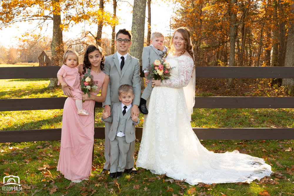 Wedding formal photo of bride and her children in Zuka's Hilltop Barn by Vision Balm in Charleston, SC.