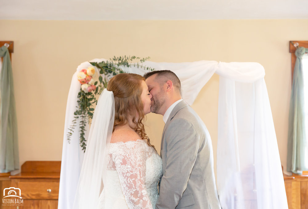Wedding photo of bride and groom kissing at the ceremony in Zuka's Hilltop Barn by Vision Balm in Charleston, SC.