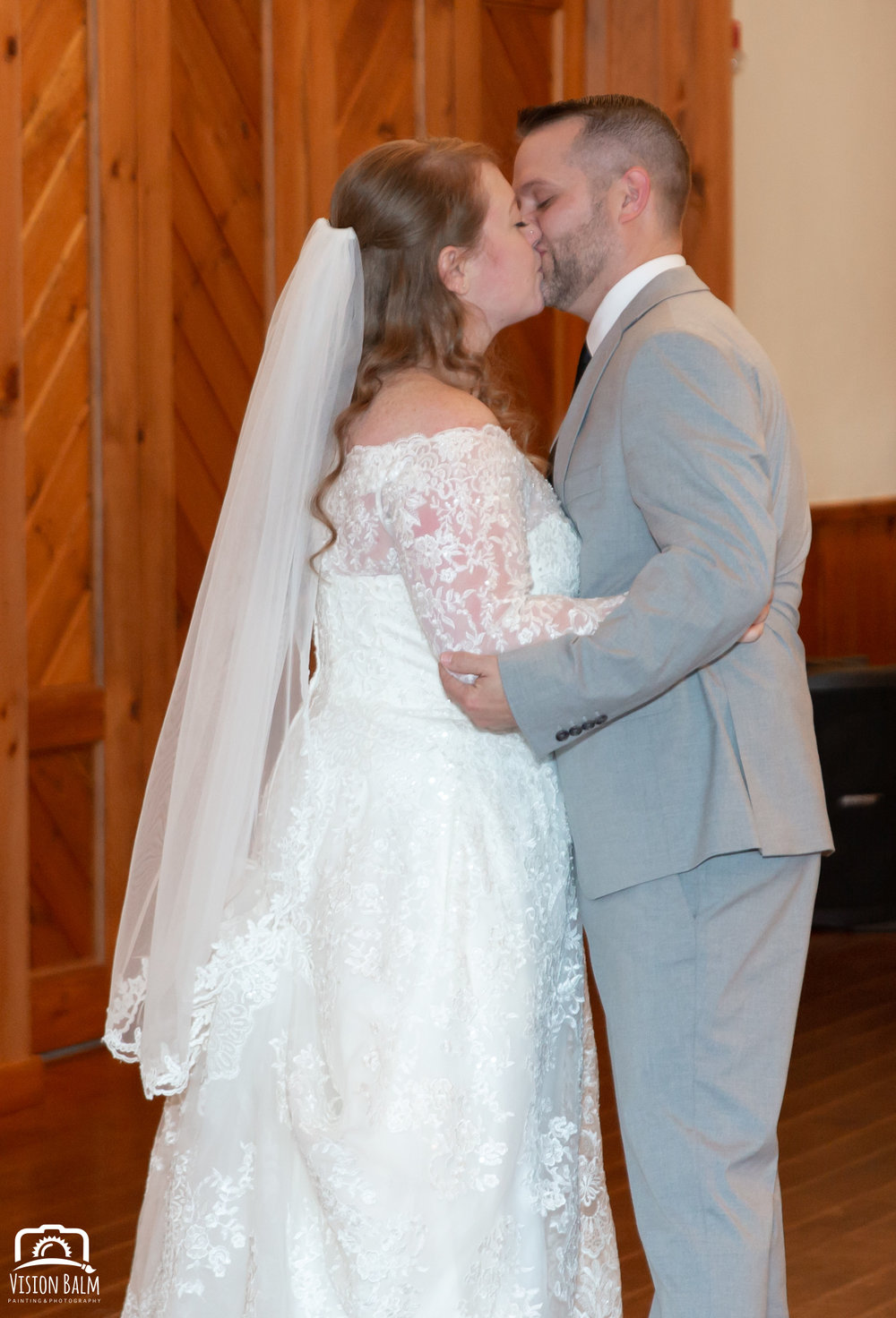 Wedding photo of bride and groom kissing in the venue of Zuka's Hilltop Barn by Vision Balm in Charleston, SC.